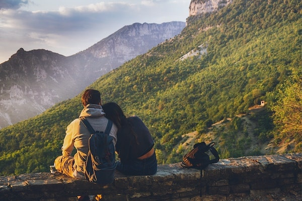 heterosexual couple sitting on stone wall, backpacking in mountains