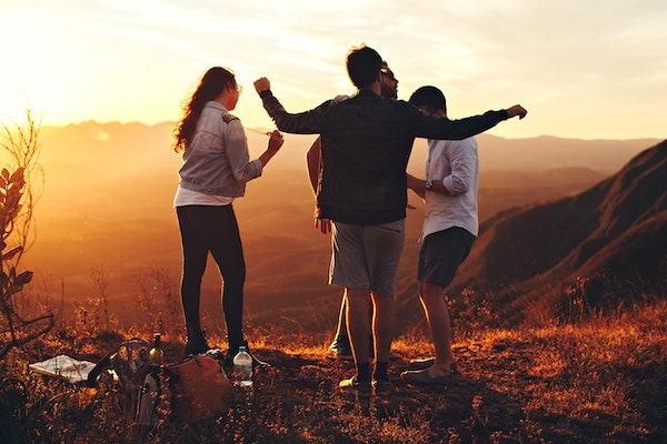 young adults celebrating on a hillside summit at sunset