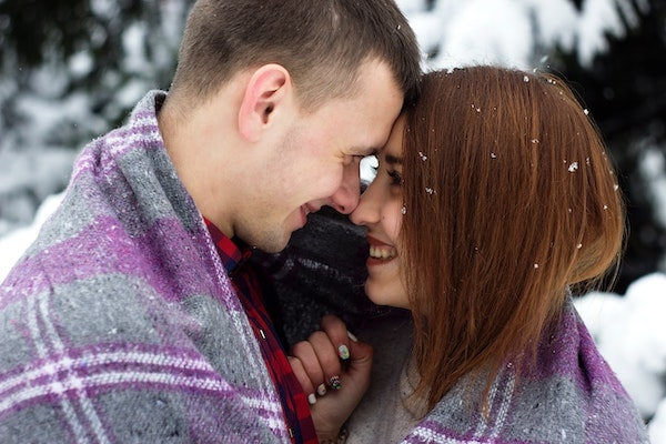 happy couple face to face wrapped in a blanket outside in a snowy scene