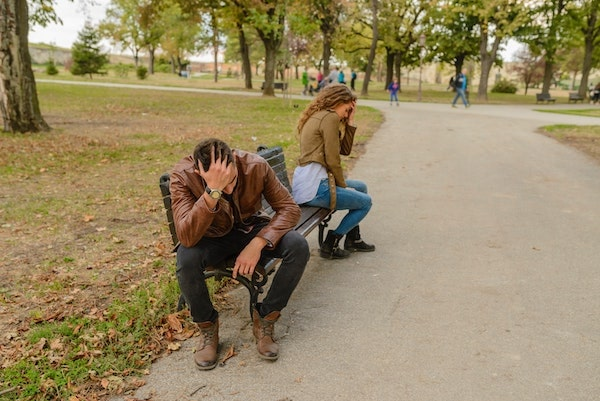 couple at odds, sitting on park bench