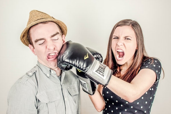 Heterosexual couple fighting with boxing gloves