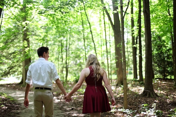 couple walking through forest holding hands