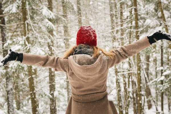 woman wearing red hat celebrating in snow