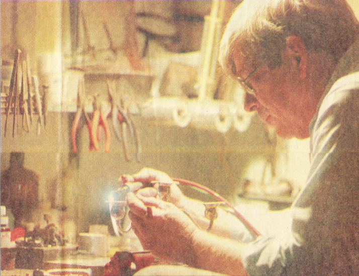 Bill Wiebold uses a torch for work on a sterling silver candlestick in his Terrace Park restoration shop.