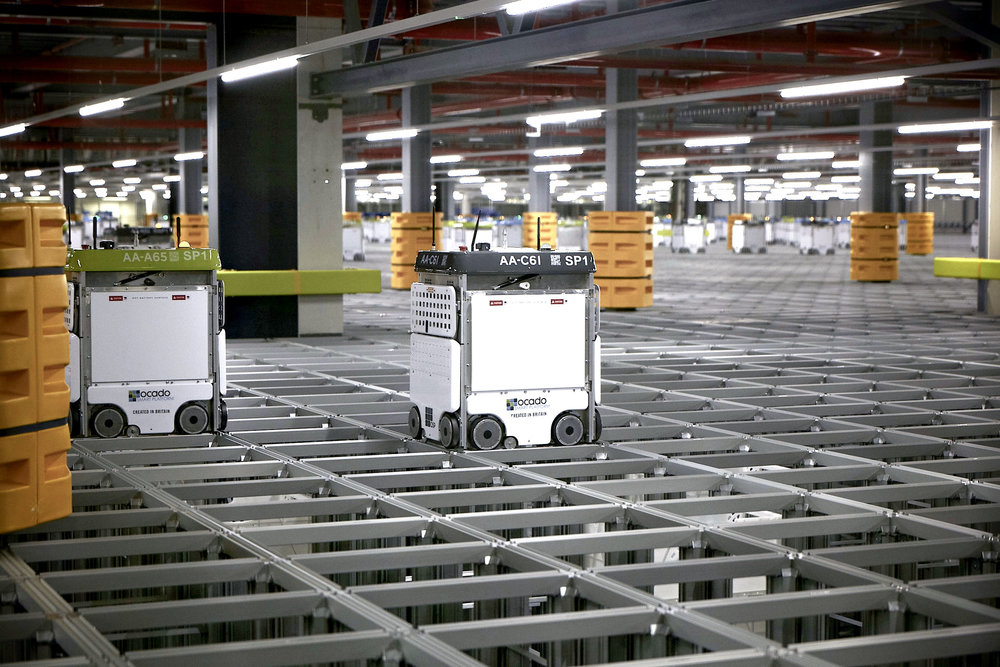 Bots collect totes stored in stacks beneath the grid