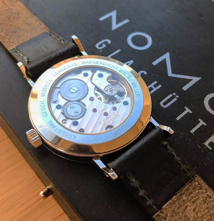 A Nomos Alpha calibre, seen through the exhibition caseback of a Tangente.