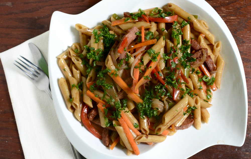 Rasta Pasta - penne pasta sautéed with bell peppers, carrots, and cook down in a creamy coconut jerk sauce