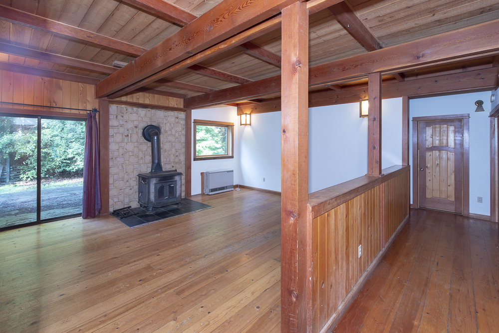 Open living room with fireplace, natural wood floors and beams.