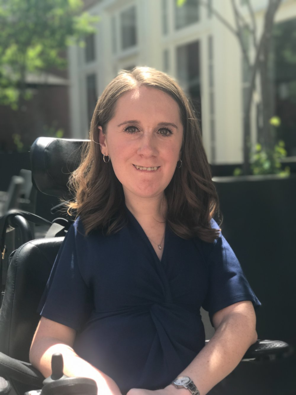 Photo of the founder, Heather Tomko, sitting outside in her wheelchair.