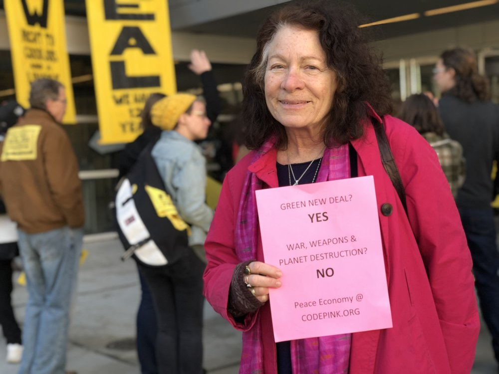 A woman holds a Code Pink sign. She urged Sunrise Movement protestors to link climate change with American militarism.