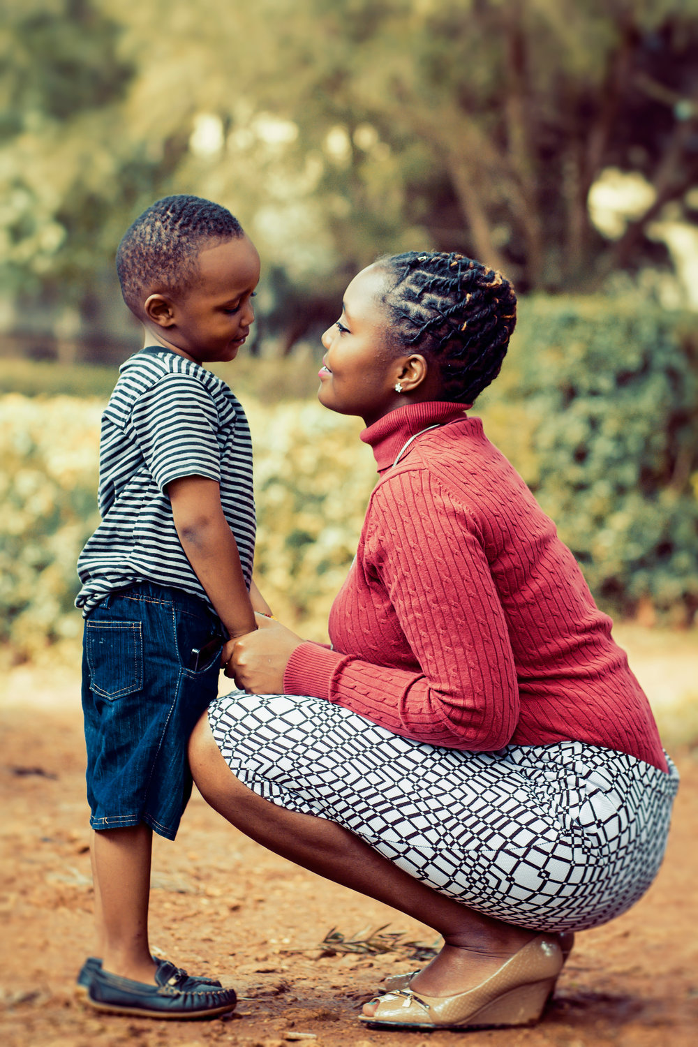 Canva - Tilt Shift Lens Photography of Woman Wearing Red Sweater and White Skirt While Holding a Boy Wearing White and Black Crew-neck Shirt and Blue Denim Short.jpg