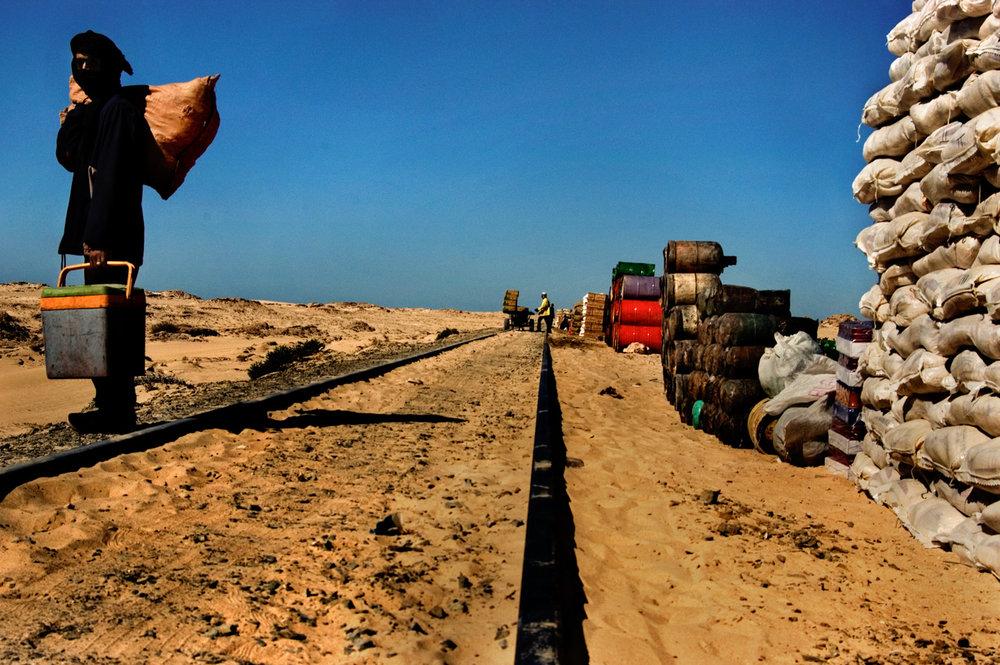 I pendolari del deserto. Viaggio in Mauritania sul treno più lungo del mondo.   Alla stazione di Nouadibou sono una trentina i paganti in attesa dell'unica carrozza passeggeri, ma allineati a fianco dei binari sono molti di più i viaggiatori che aspettano di infilarsi nei vagoni adibiti al trasporto del ferro. Proprietari di bestiame, commercianti o viaggiatori, tutta gente che conosce il treno a memoria. 2,5 km di vagoni merci, più una vettura passeggeri: è il treno più lungo al mondo.