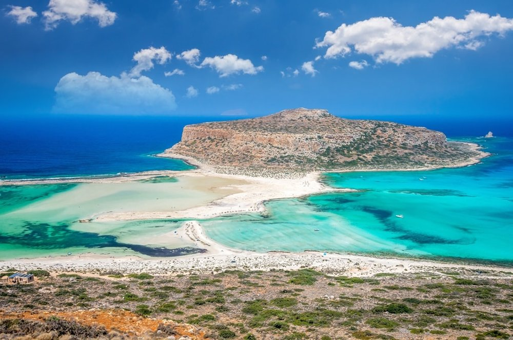 Balos-lagoon-on-Crete-island-Greece.-Tourists-relax-and-bath-in-crystal-clear-water-of-Balos-beach.-min.jpg