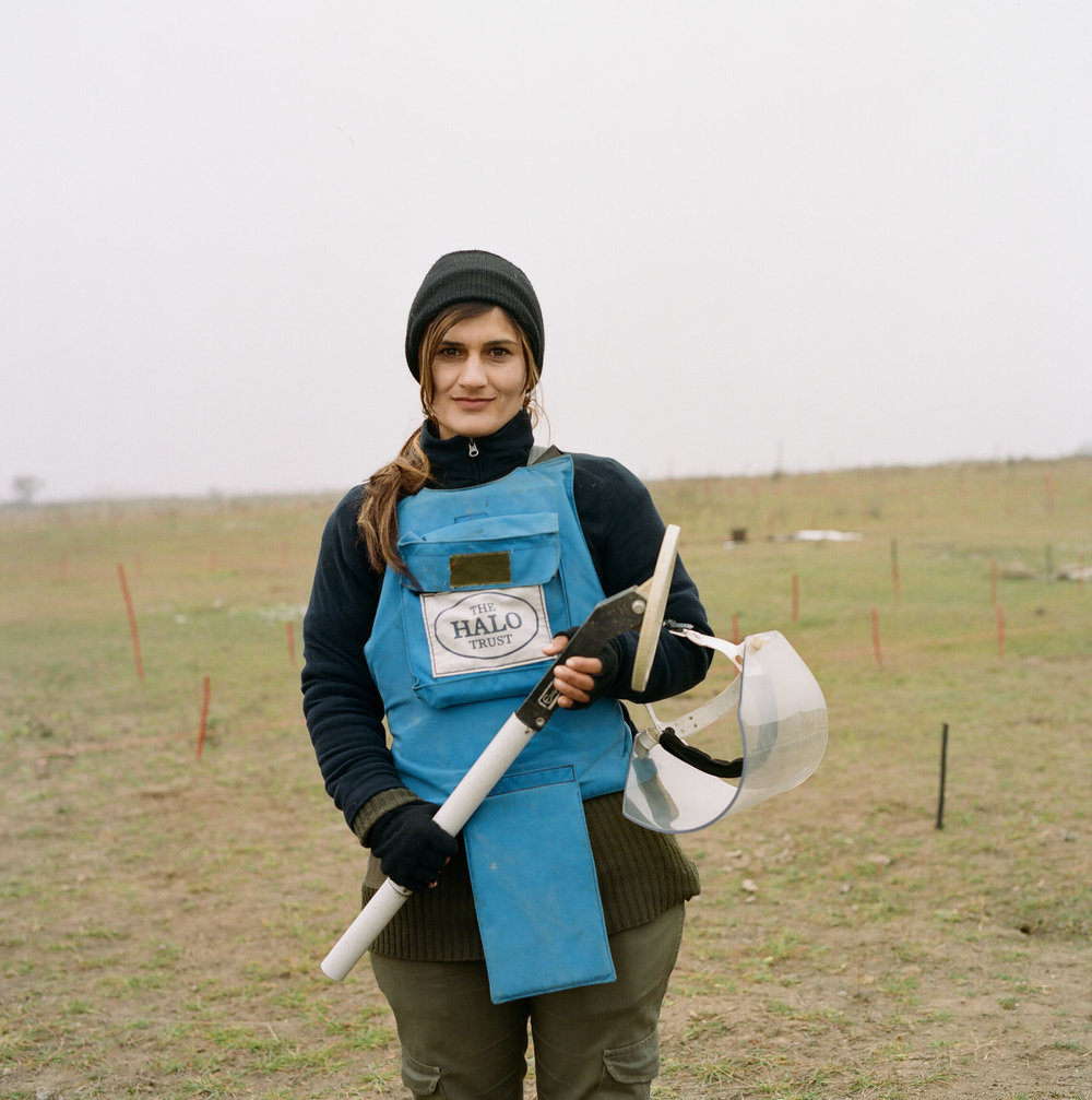 Alvina at Marzili minefield. In the background, red posts mark the boundary between cleared and uncleared land.