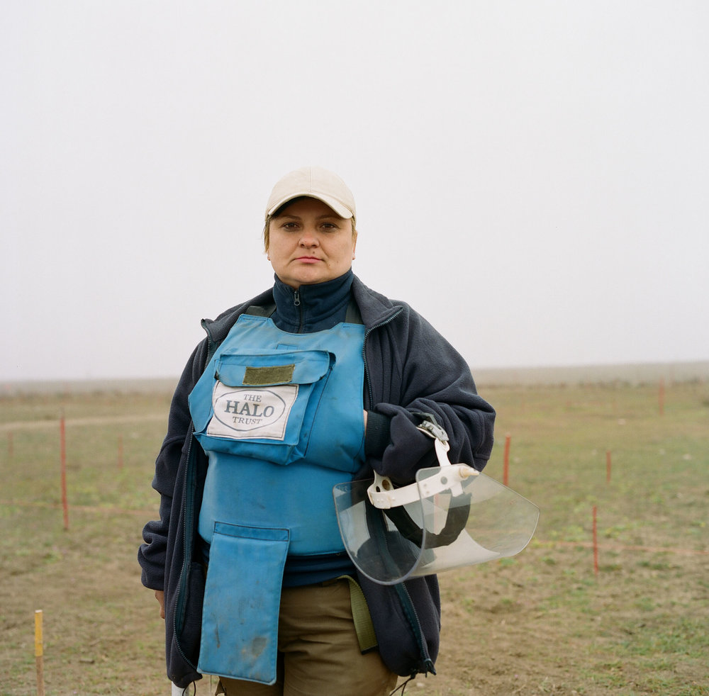 Svetlana at Marzili minefield. Behind her, red markers show the boundary between cleared and uncleared land.