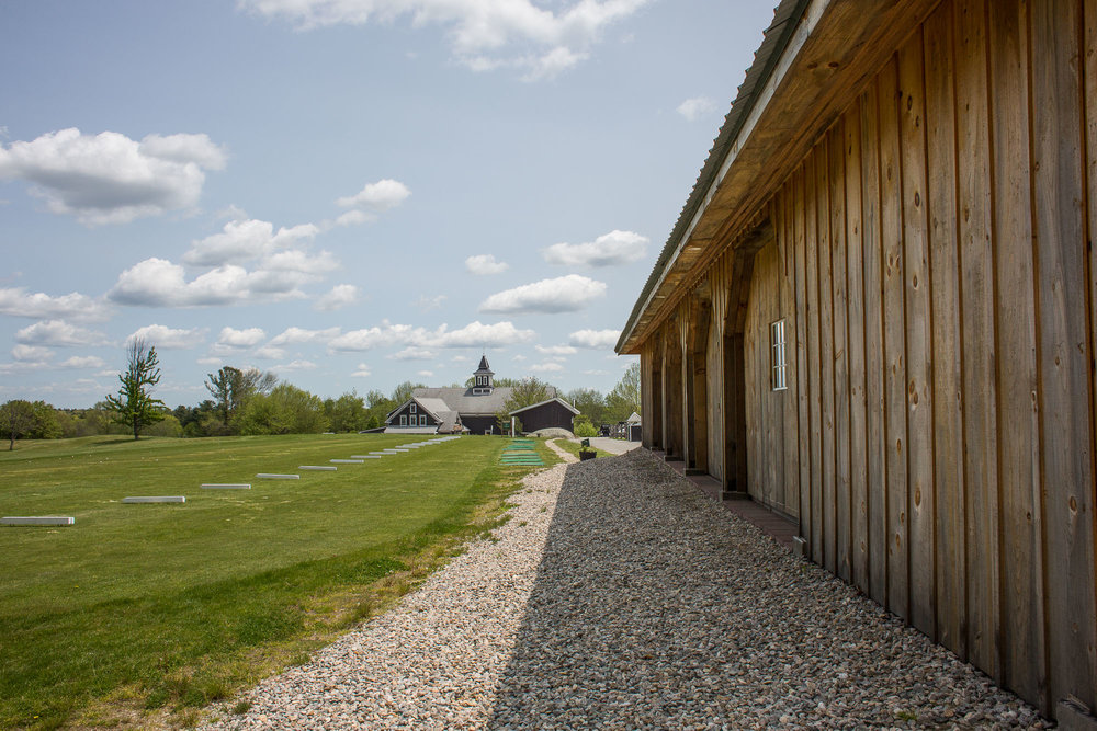 Leading lines in the gravel path, the barn building, and the driving range, all leading your eye to the building in the center of the image.
