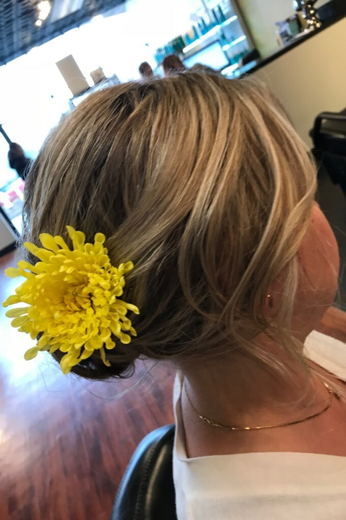 Side - Swept Flower Updo:  Everyone loves a side swept updo for a big night! This look is soft and pretty, and will gracefully frame anyone's face . The flower in the back adds a pop of color and texture, and can be carefully matched as the perfect companion to your outfit! This floral 'do will be sure to make you and your look stand out for a special night.