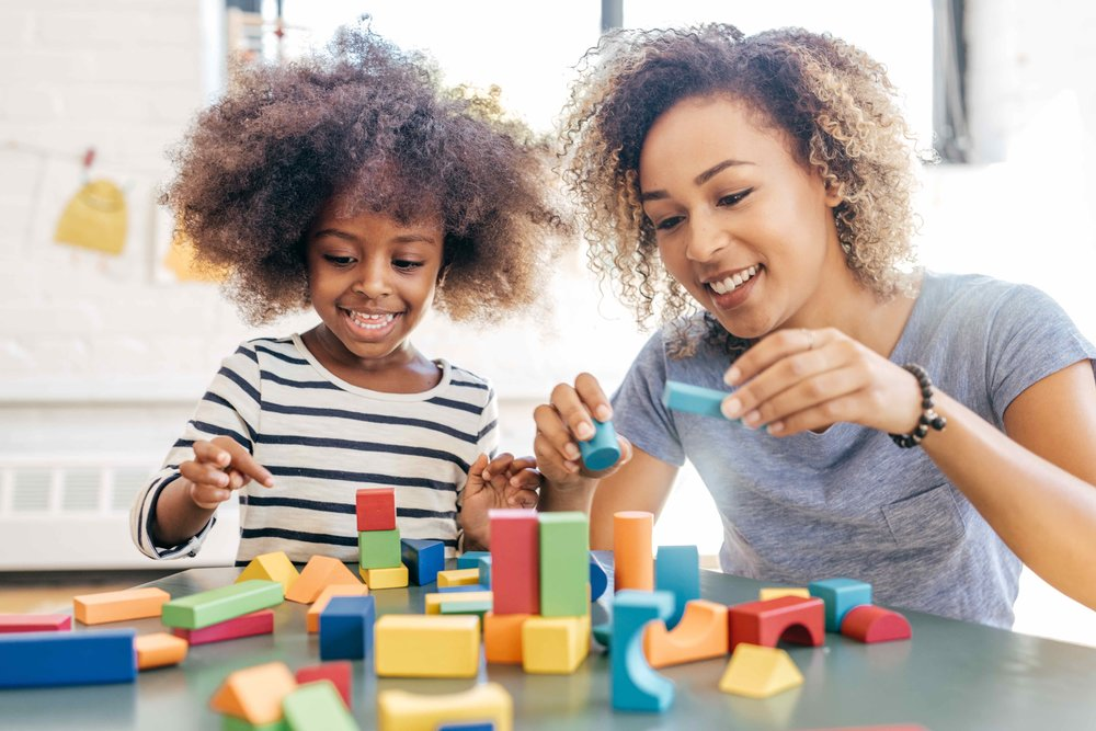 Picture of therapist using blocks to play with little girl.