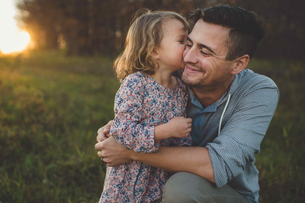 Picture of daughter giving dad a kiss.