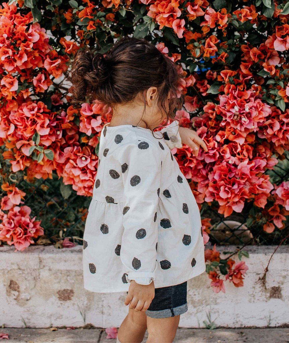 Picture of little girl playing with flowers.