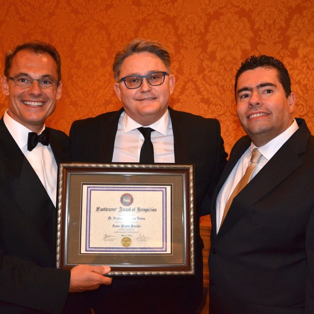 Tony Viazis (left), the inventor of FASTBRACES® , presenting Stephan van Vuuren (middle) with the Senior Master Provider award in Dallas in 2016. On the right is Evangelos Viazis, who has done some magical work with FASTBRACES® in his practices in Athens.     Stephan van Vuuren receiving the Annual Viazis Award 2017 from Dr Tony Viazis for the dentist that can move teeth the fastest in the world with  FASTBRACES ®