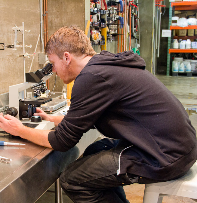 Bryce Tyranski, brewer at Fort Point checking out yeast activity in the microscope