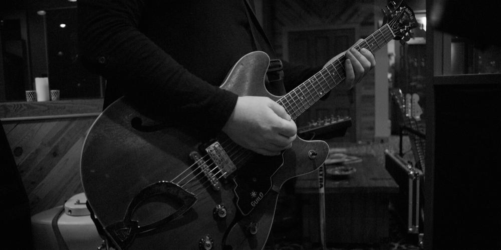 A001_C013_0102S6.0000478 Eric Jerardi RED Guitar.png