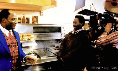 In the fast-food restaurant, Murphy and John Amos position themselves as photographers prepare to shoot the scene.