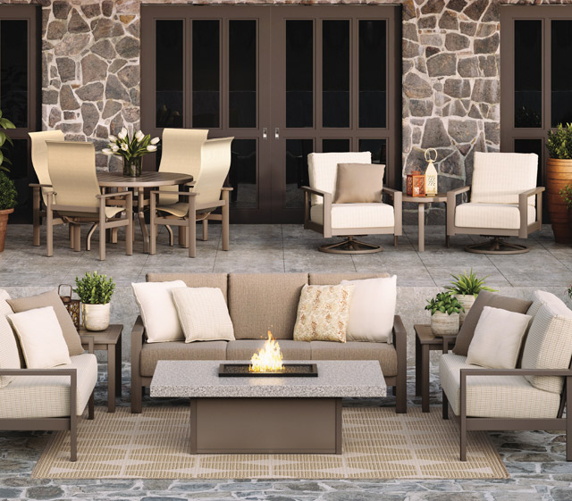 Homecrest Elements cushion aluminum frame collection sofa, loveseat & Lounge chair with rectangle firepit. Two Elements cushion swivel lounge chairs with side table. Four Elements sling dining chairs with round dining table.