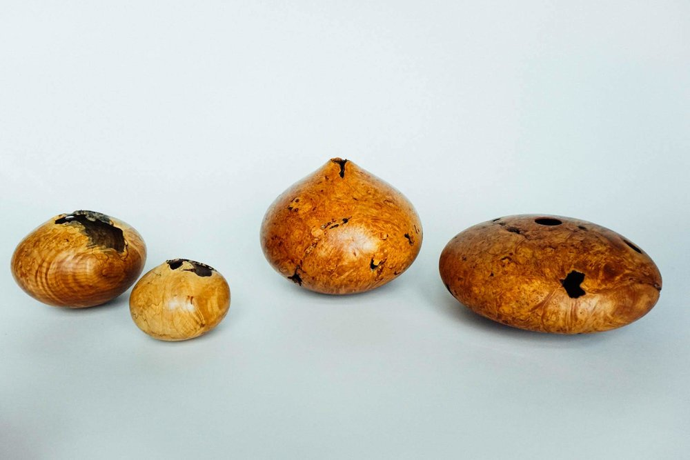 An arrangement of hollow forms in maple burl.