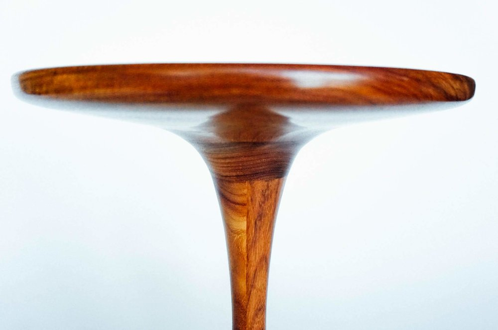 The top is turned to a thickness of approximately 5/8 inch to provide a delicate look to the table.