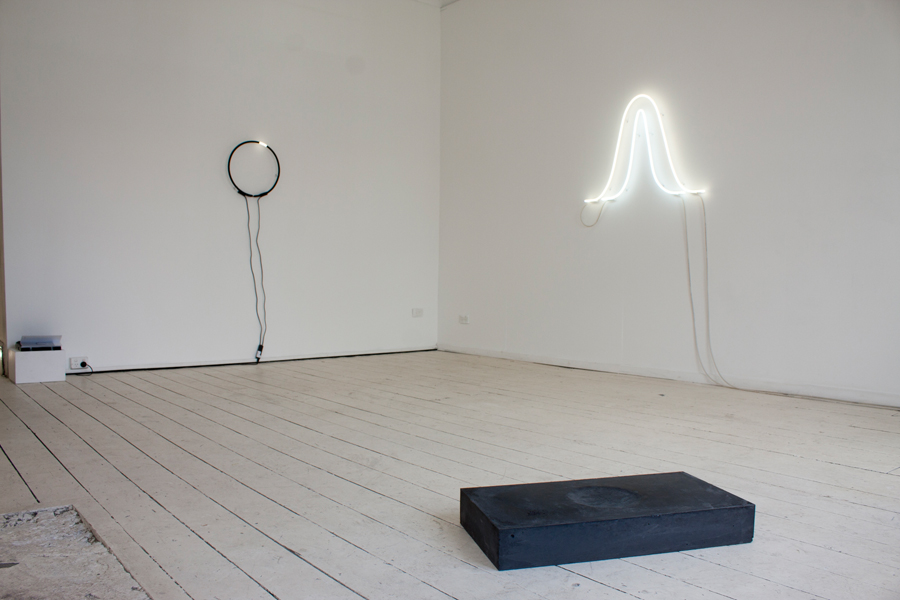 Installation view in 'Steady Illiterate Movement', Seventh Gallery, Melbourne   (left to right) 'white white (summer and winter solstice)', 2017, neon light, electrical components, 70 x 100cm; 'Hora Somni: for Vera Rubin', 2017, cast black concrete with Papaver Somniferum seeds, 10 x 35 x 70cm