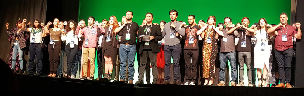 Full stage of Mexicanx Initiative members Xing up during the opening ceremonies at Worldcon 76 (Sent by John Picacio; photo by Debi Chowdhury)