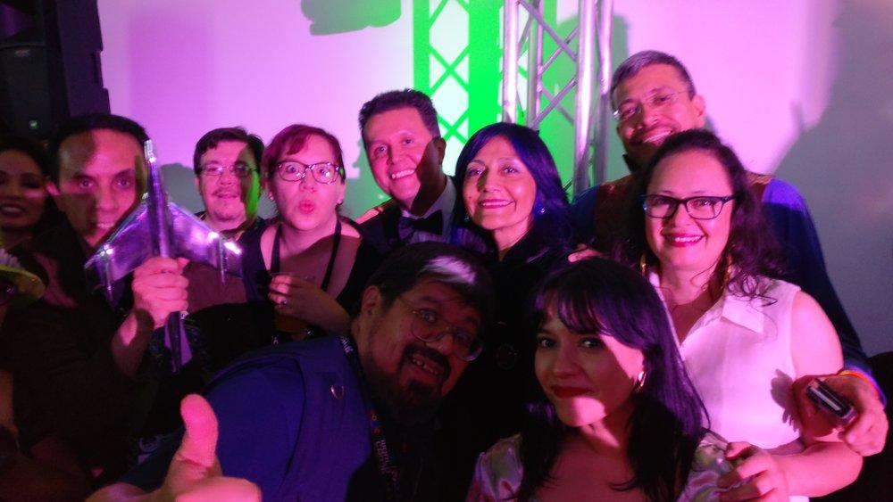 Alberto Chimal holding John Picacio's Alfie Award with David Bowles, Raquel Castro, John Picacio, Patty Garcia, Héctor González, Libia Brenda, Gabriela Damián Miravete, and José Luis Zárate (Photo by Anonymous on Alberto's phone)