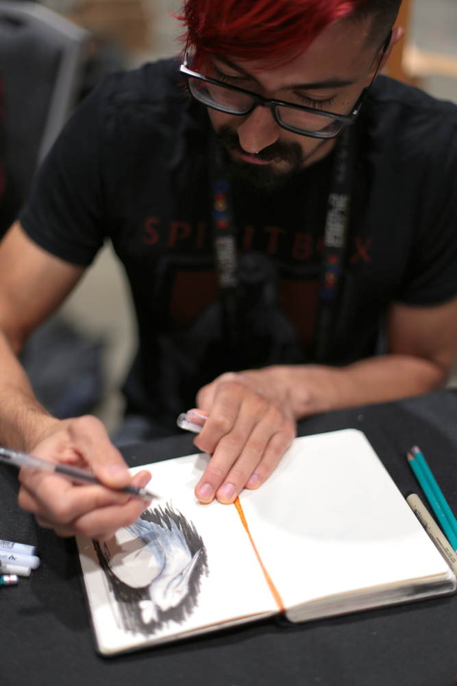 Cody Jimenez sketching at the Mexicanx Initiative art booth during Worldcon 76 (Photo by Dianita Cerón)