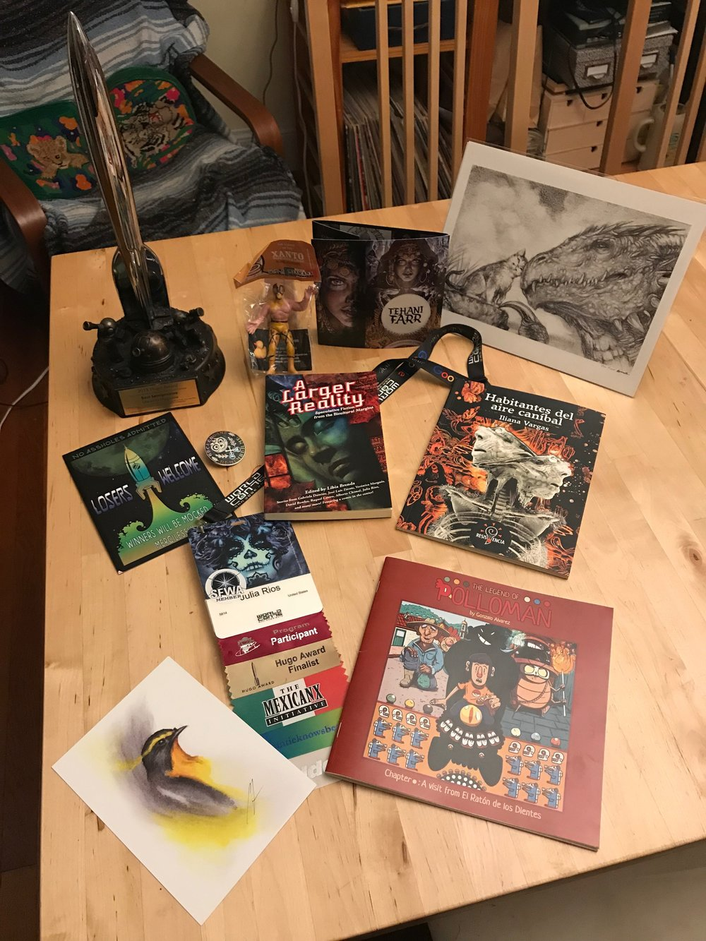 A haul of Mexicanx Initiative works and Worldcon 76 mementos Julia Rios cherishes. Back left to right: Hugo Award with base designed by Sara Felix and Vincent Villafranca, lucha libre figure from José Luis Zárate, art of Tehani Farr, kitty and drago print by DIanita Cerón. Middle left to right: Invitation to the Hugo Losers Party, *Coco* enamel pin, a copy of *A Larger Reality*, *Habitantes del aire canníbal* by Iliana Vargas. Bottom left to right: Bird art print by Cody Jimenez, Julia Rios's Worldcon 76 name badge with art by John Picacio and a Mexicanx Initiative ribbon, *The Legend of Polloman* by Gonzalo Alvarez. (Photo by Julia Rios)