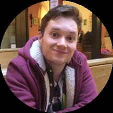 Jonge man met lichtbruin haar, lichtpaarse hoodie kijkt opgewekt in een café.