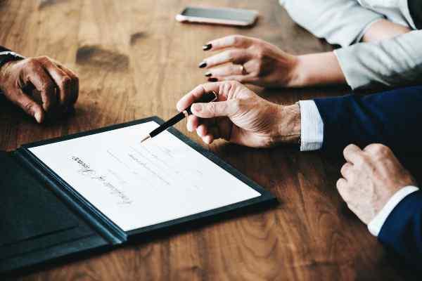 Startende ondernemer in blauw kostuum ondertekent met zwarte pen de oprichtingspapieren voor zijn onderneming bij een notaris samen met zijn advocate.