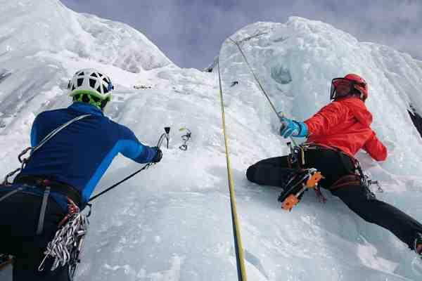 Twee bergklimmers leven hun droom en passie met rode en blauwe jassen op een witte berg