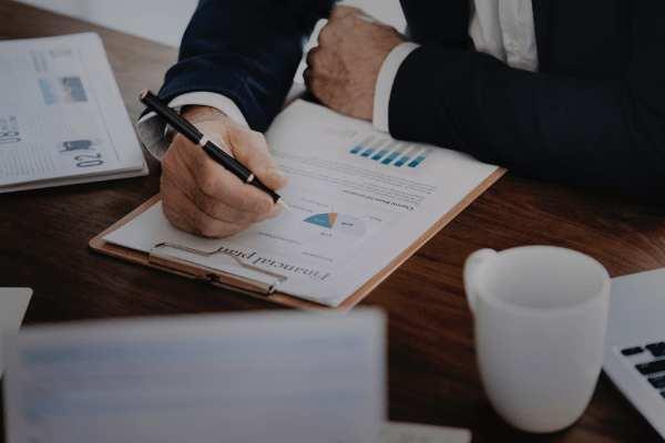 Man in donkerblauw kostuum met pen in de hand neemt zijn ondernemingsplan en financiële analyse door terwijl hij koffie drinkt met zijn grijze laptop naast hem