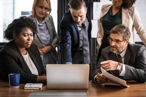6 experten in formele kledij zitten aan een tafel in hout en nemen de startersplannen op de laptop van een beginnende ondernemer door tijdens een infomoment.