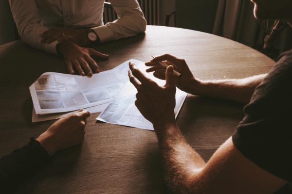 2 beginnende ondernemers zitten aan een houten tafel met documenten en krijgen feedback van een expert met horloge en wit hemd tijdens een infomoment