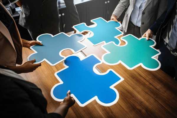 Experts in formele kledij houden tijdens een brainstormsessie blauwe puzzelstukken vast en proberen ze in elkaar te schuiven als oefening.