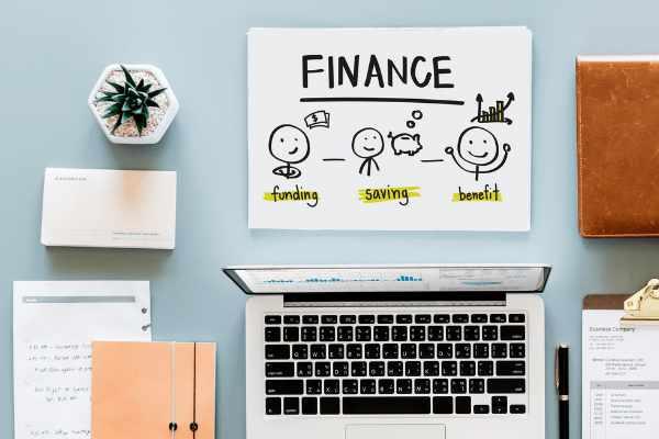 """Een lichtblauwe tafel met plant, notities, agenda, laptop en een financieel plan met drie figuren die """"funding"""", """"saving"""" en """"benefit"""" visueel duidelijk maken."""
