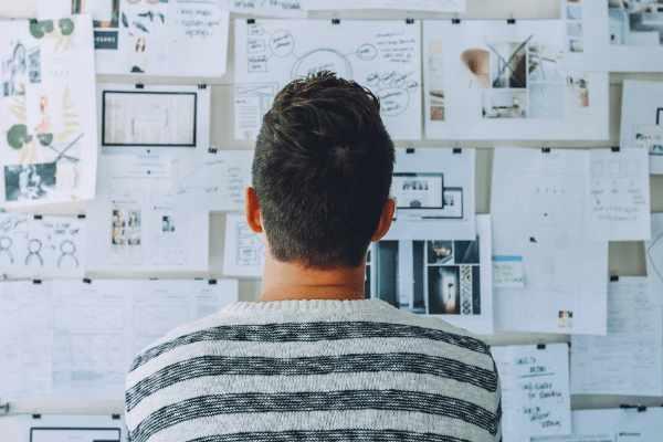Beginnende zelfstandige met gestreept wit-blauwe sweater staat voor zijn whiteboard en doet aan brainstorming om een goed idee voor zijn onderneming uit te werken.