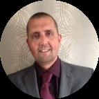 Man glimlacht voor een wit-grijze achtergrond in paars hemd met das en donkergrijze blazer.