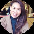 Vrouw van Aziatische achtergrond met bruin haar zit met de handen gevouwd in een bruine sweater en donkerblauwe turtleneck in een café.