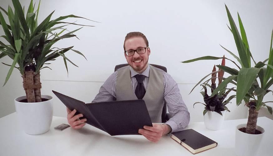 Kevin Sanders in grijs kostuum in wit bureau van Anders met Sanders met ondernemingspapieren, planning en planten op de achtergrond.