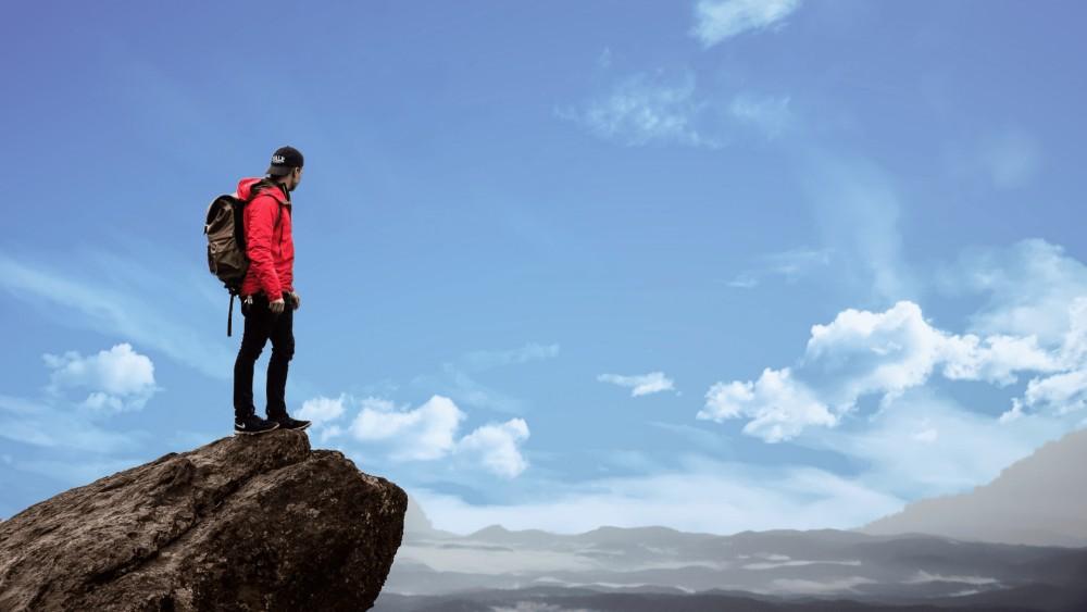 Man met rode jas en donkerbruine tas staat op een rots in zwarte jeans met blauwe wolken en de lucht op de achtergrond.