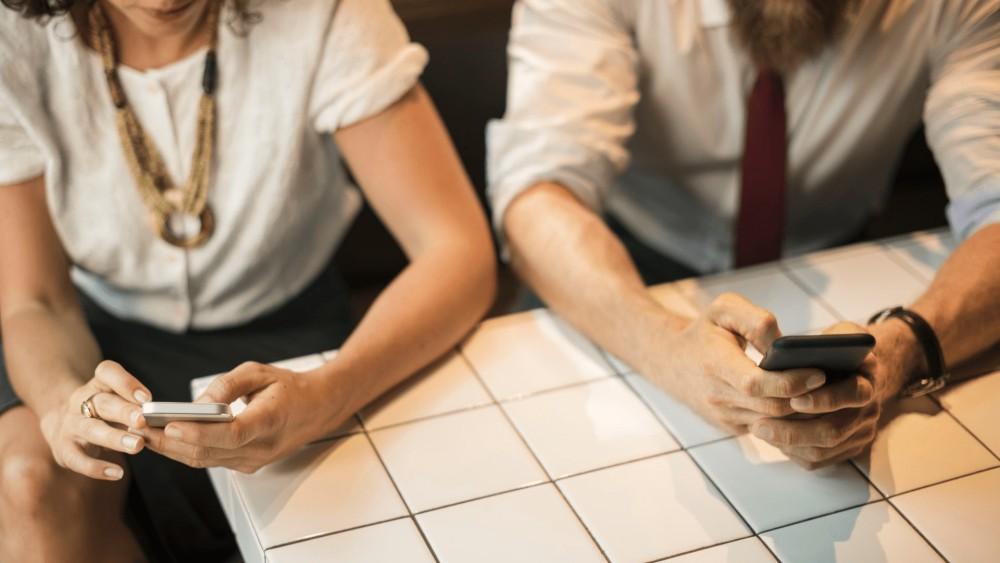 Een man en een vrouw in formele witte kledij zitten aan een keukentafel in witte steen met hun smartphones in de hand, afgeleid.